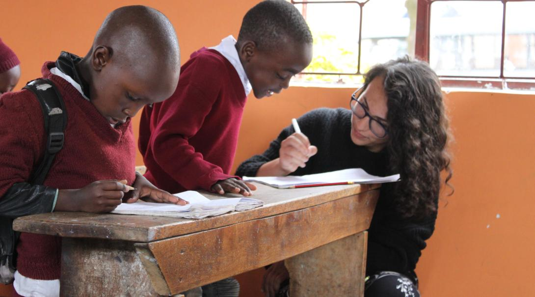 A volunteer teaching abroad helps a child complete an activity at a school in Tanzania, Africa.